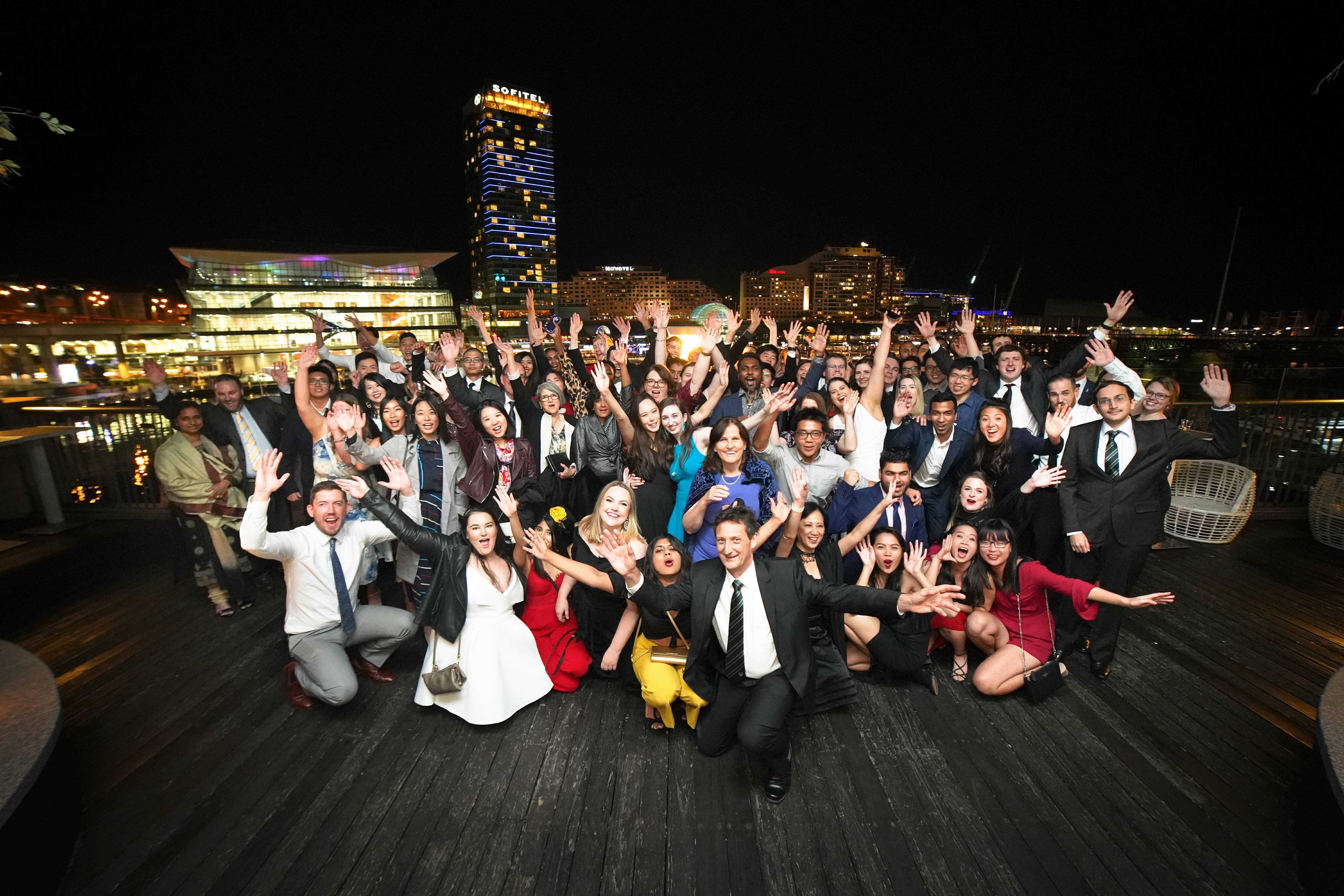 Photograph of residents enjoying a function at night by the harbour with city lights in the background