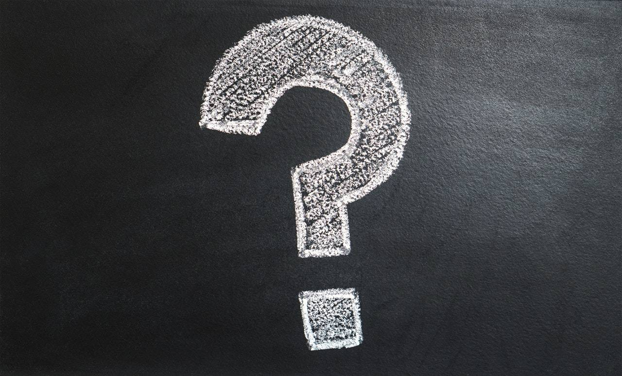 Photograph of a question mark drawn in chalk on a black board
