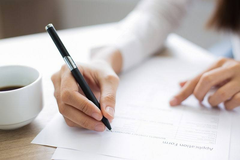 Photograph of hands holding a pen and filling out an admission form