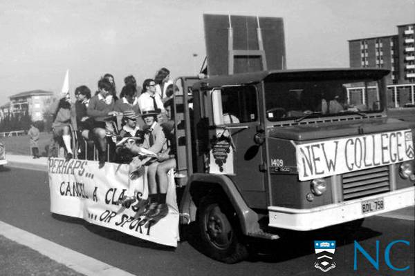 Black and white photograph - College residents riding a large flatbed truck with a banner