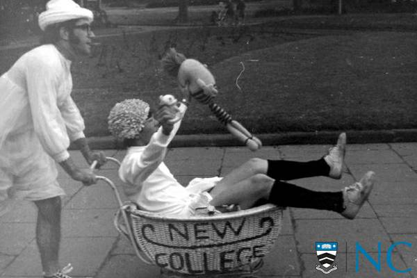 Photograph of college resident being pushed in a baby pram with New College emblazoned on the side